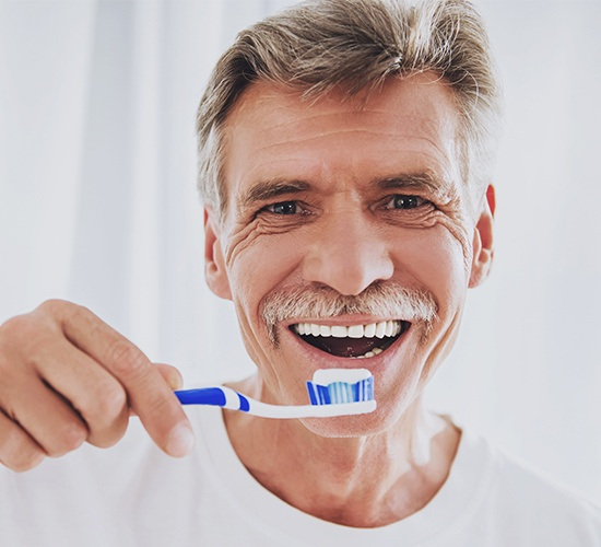 man holding toothbrush and smiling