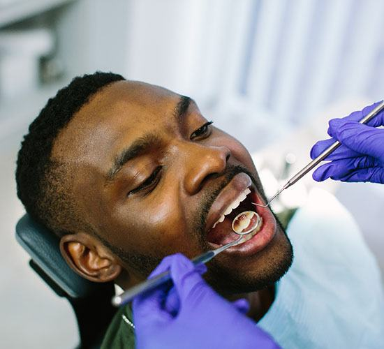 A young man receives a dental checkup during a regular appointment with his dentist