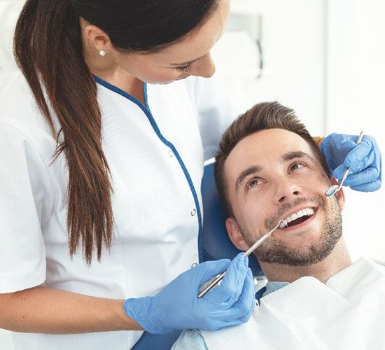 A dental hygienist prepares to start a dental cleaning while the male patient smiles