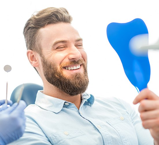 man checking smile in blue mirror