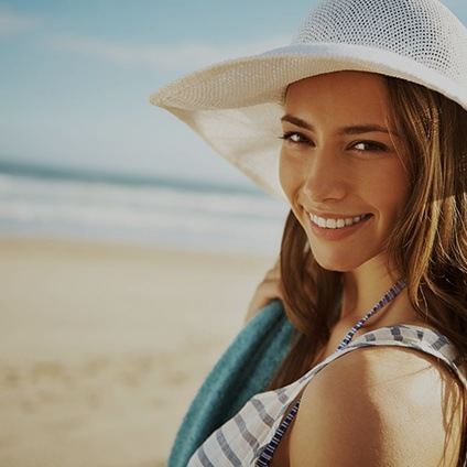 woman with sunhat smiling on beach