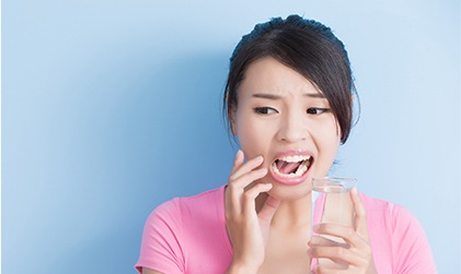 Woman with cavity holding glass of water